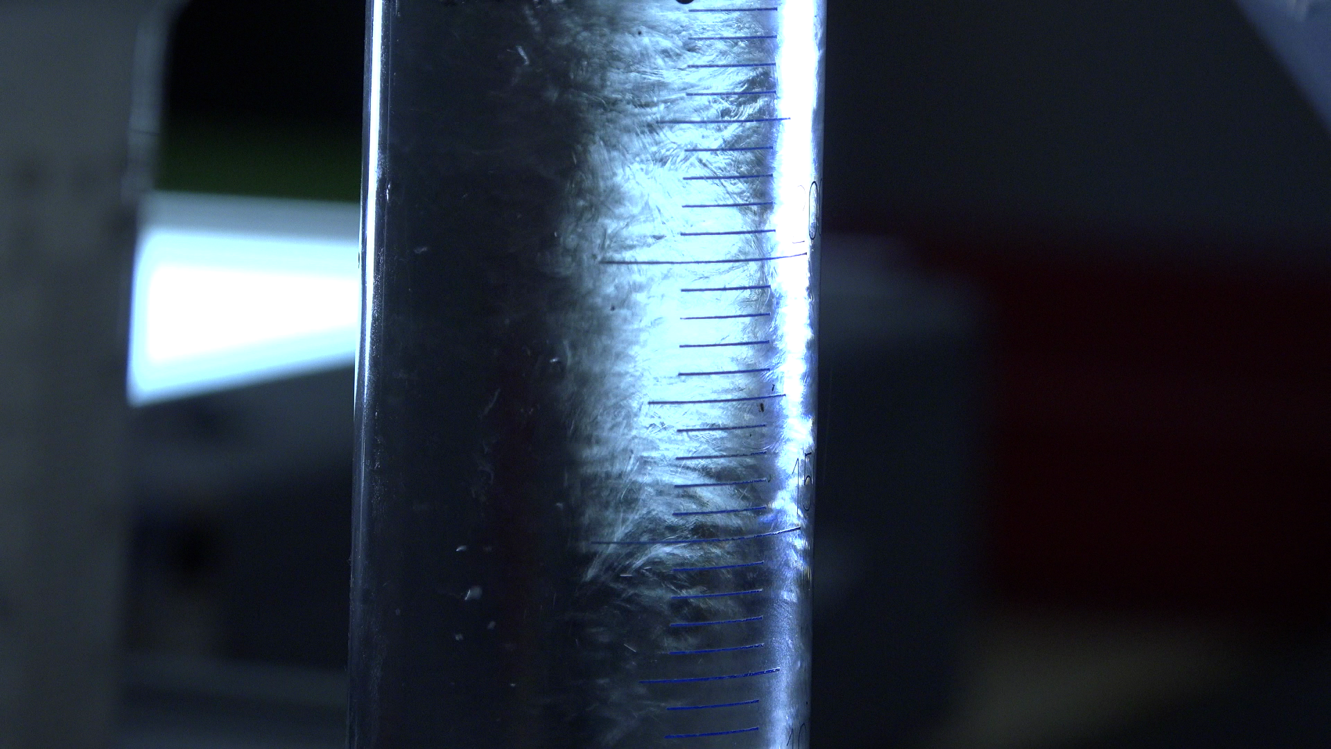 Still from the film Een Donker Uitzicht. It's a extreme close-up of a vial with developing liquid, used to develop film. It looks dreamy, almost magical.