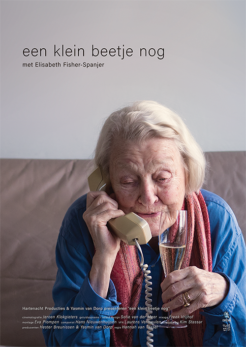 Poster from the film Een klein beetje nog. Elisabeth is sitting on her couch with her phone in one hand and a glass of champagne in the other.