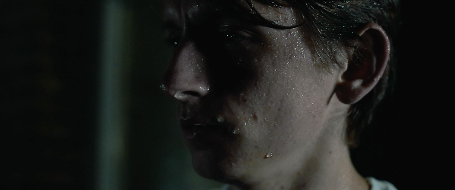 Still from the film Gesloten Deuren. It's a close-up of Jasper standing in the rain.
