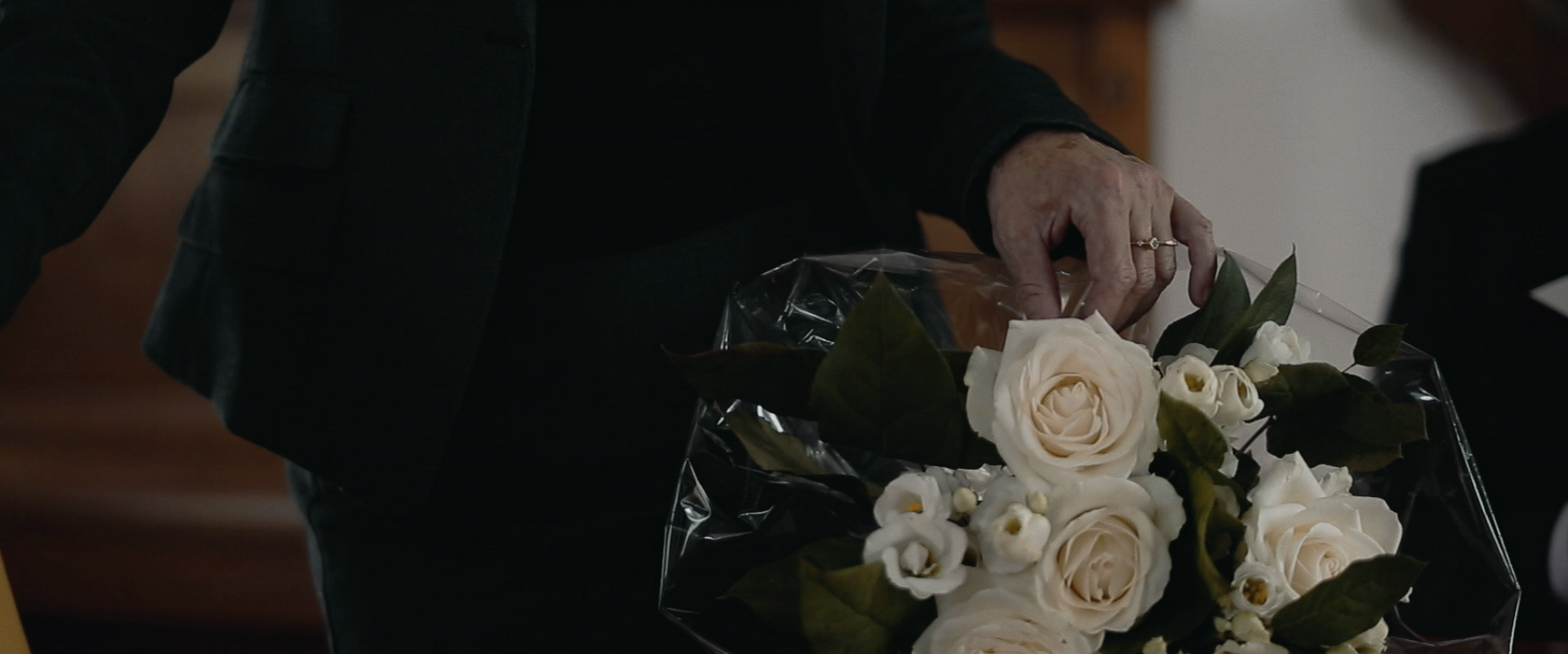 Still from the film Gesloten Deuren. It's a close-up of the mother standing by a bouquet of white flowers.