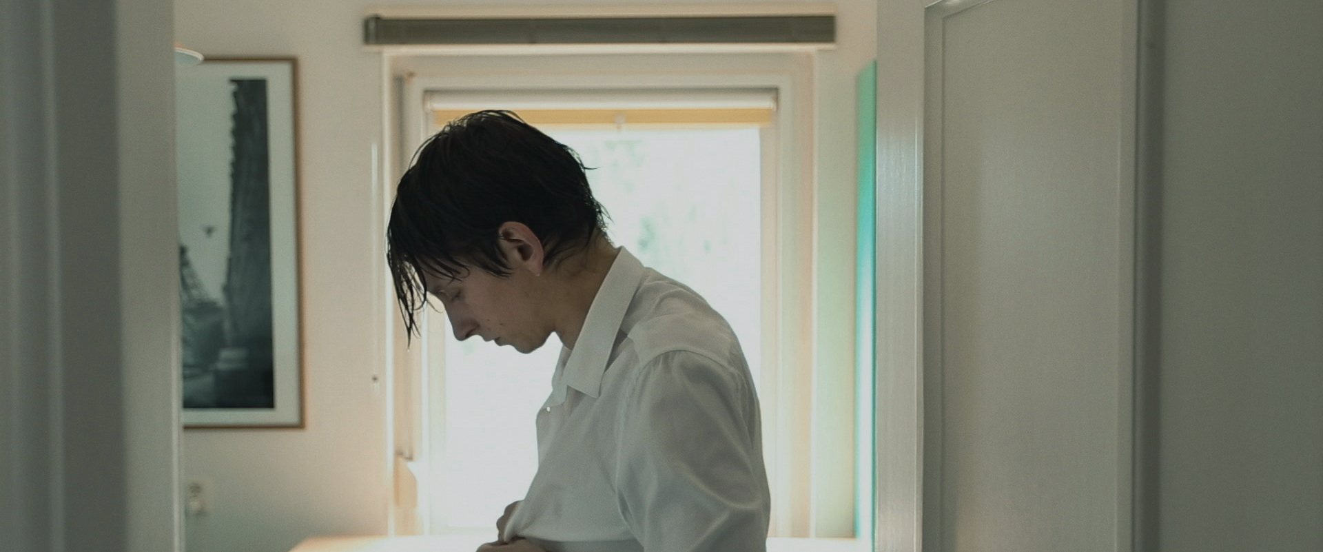 Still from the film Gesloten Deuren. It's a profile shot of Jasper standing in his room changing his clothes for the funeral.