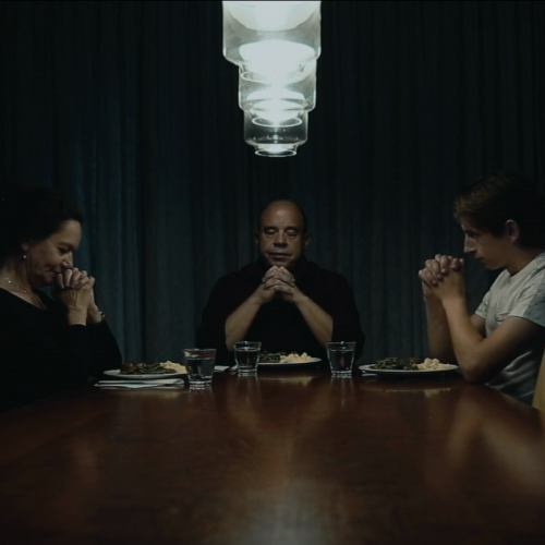 Still from the film Gesloten Deuren. The father is at the head of the table, the mother on the left and Jasper on the right. They are holding their hands in prayer.