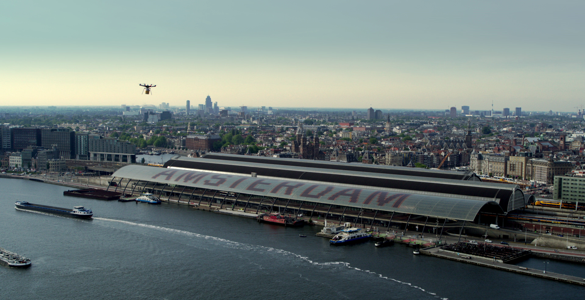 Still from the promo video Hilton Haring Party. An aerial shot overlooking Amsterdam Central Station. A drone is seen approaching the station.
