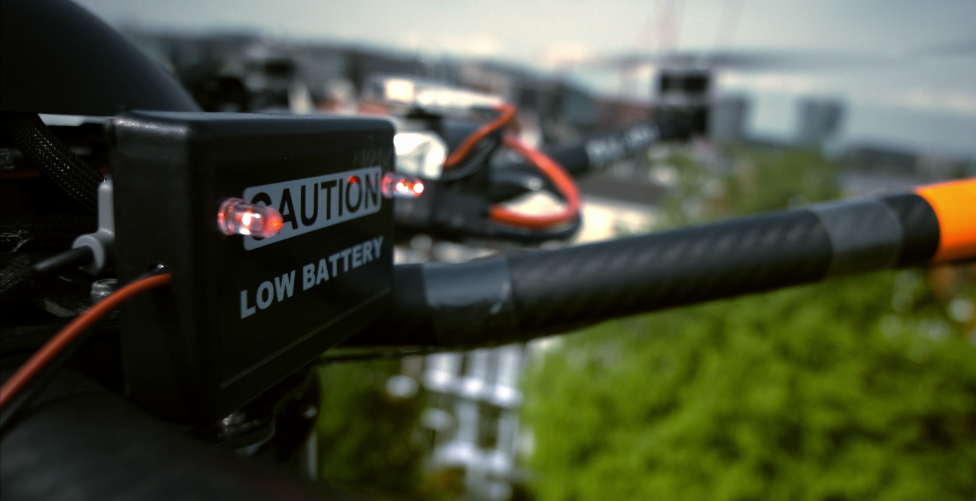 Still from the promo video Hilton Haring Party. A close up shot of the battery pack blinking red, saying 'caution: low battery'.
