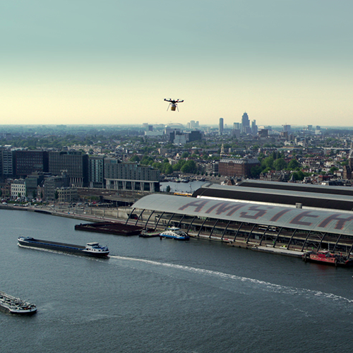 Thumbnail for the promo video Hilton Haring Party. An aerial shot overlooking Amsterdam Central Station. A drone is seen approaching the station.