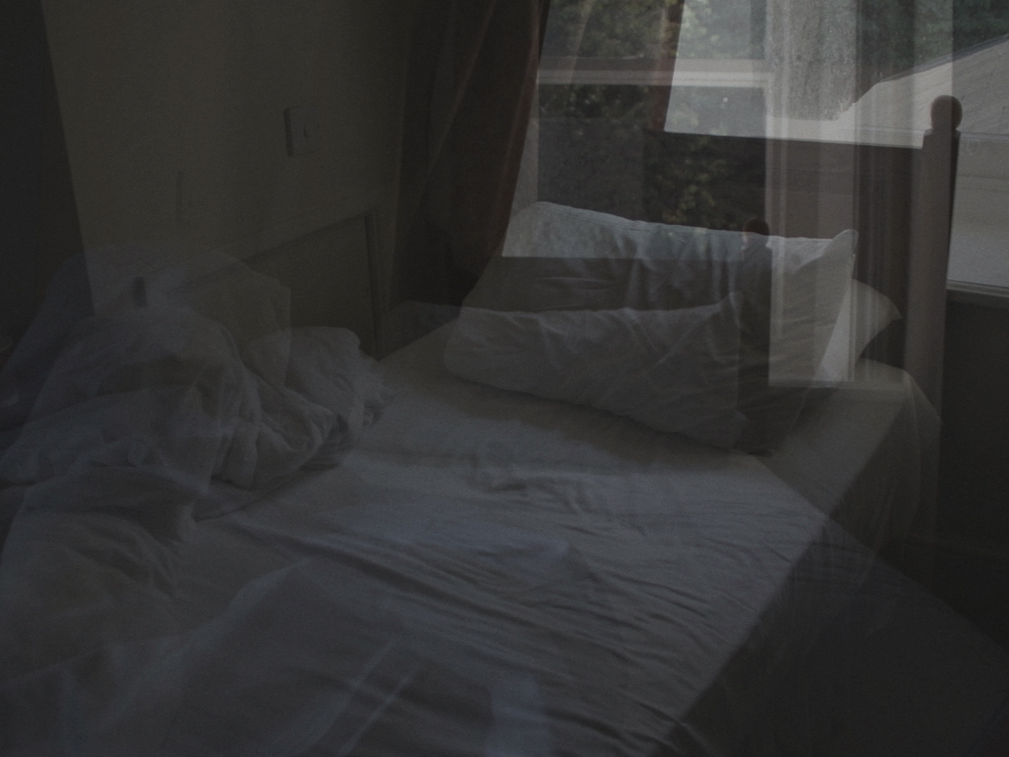 Still from the poetry film Morning. Two shots of a bed are blended together to create a wistful shot.