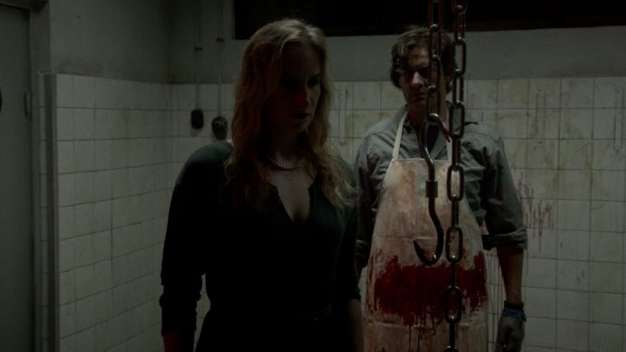 Still from the film Nachtwerk. Rosa and Herman are in the back room of the butchery. Rosa is seen in the front, blurry, while Herman stands behind her with a bloody apron, menacingly. The room is dimly lit.
