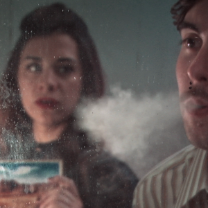 Still from the film Nowhere Place. The writer and the girl are seen in the reflection of a mirror. The writer blows smoke on the mirror and the girl is holding a postcard of a landscape.