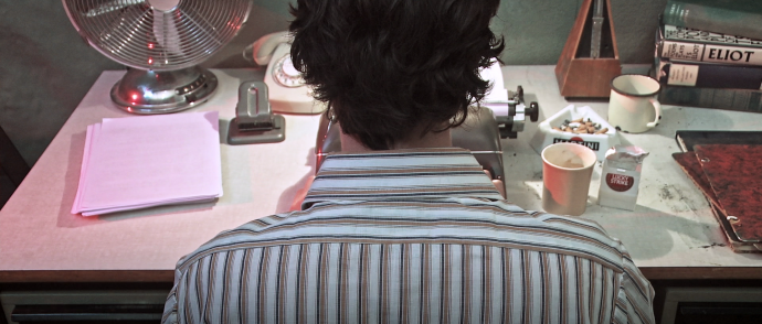 Still from the film Nowhere Place. The writer is sitting in front of the typewriter and we are seeing the back of his head and his shoulders.