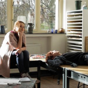 Still from the film Ne Me Quitte Pas. Patrick and Angelique are sitting and lying on the worktables in an art workroom.