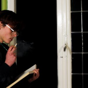 Still from the film Ne Me Quitte Pas. Patrick is standing in the window of his room, writing.