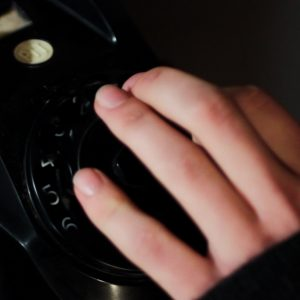 Still from the film Ne Me Quitte Pas. It's a close-up shot of Patrick's hand on the dial of an old rotary phone.