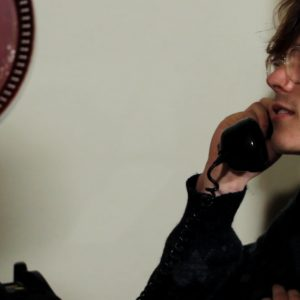 Still from the film Ne Me Quitte Pas. Patrick is seen from the side, calling Angelique.
