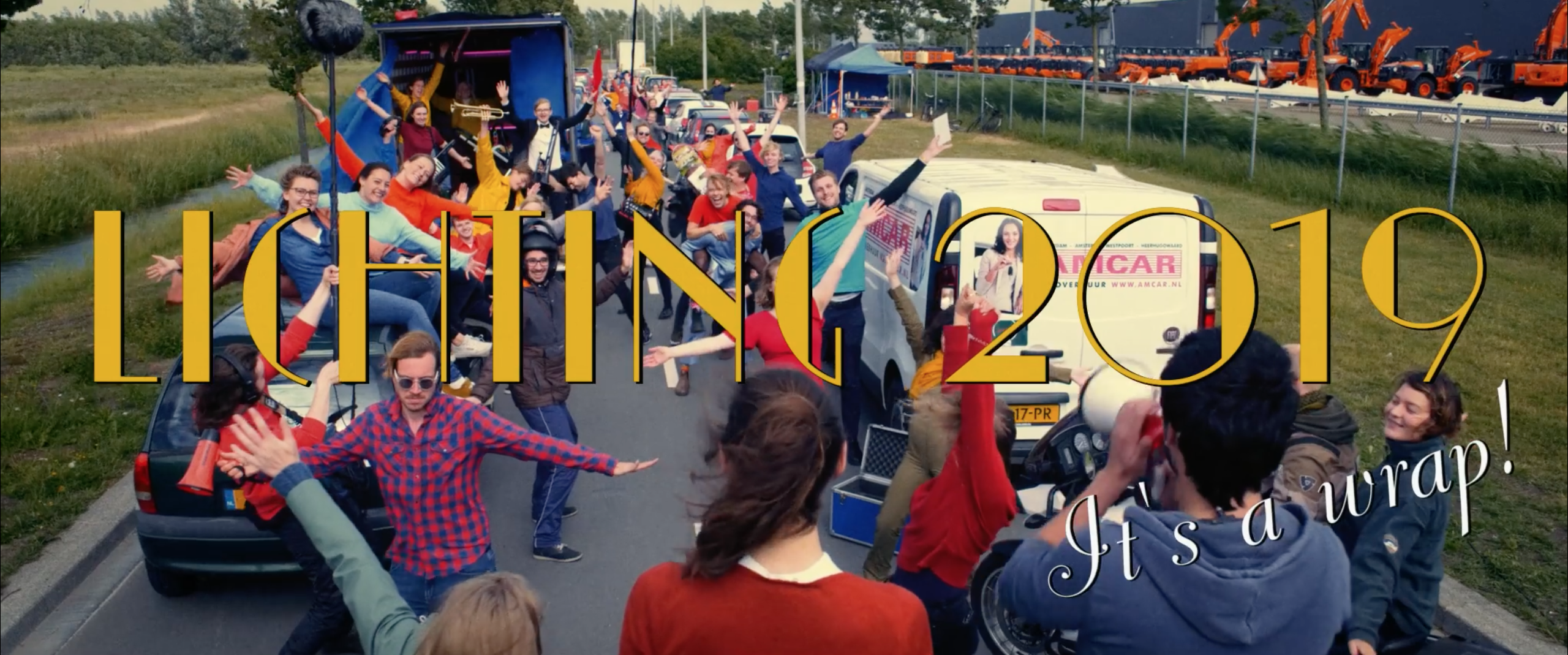 Still from the promo film Nieuwe Dag Op Set. It's a wide shot of a road filled with people and cars. There's a big title that says