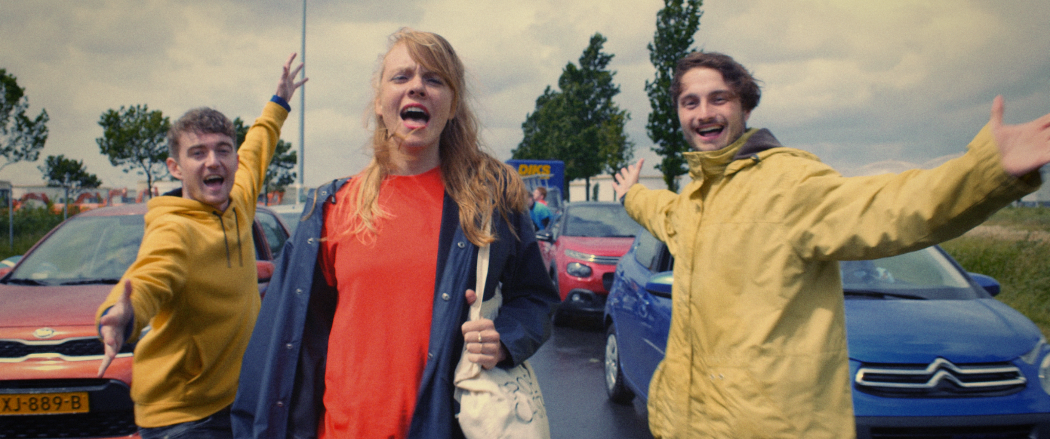 Still from the promo film Nieuwe Dag Op Set. There are three people walking in between cars on a busy highway. The girl in front seems to be singing and the two boys besides her are doing jazz hands.