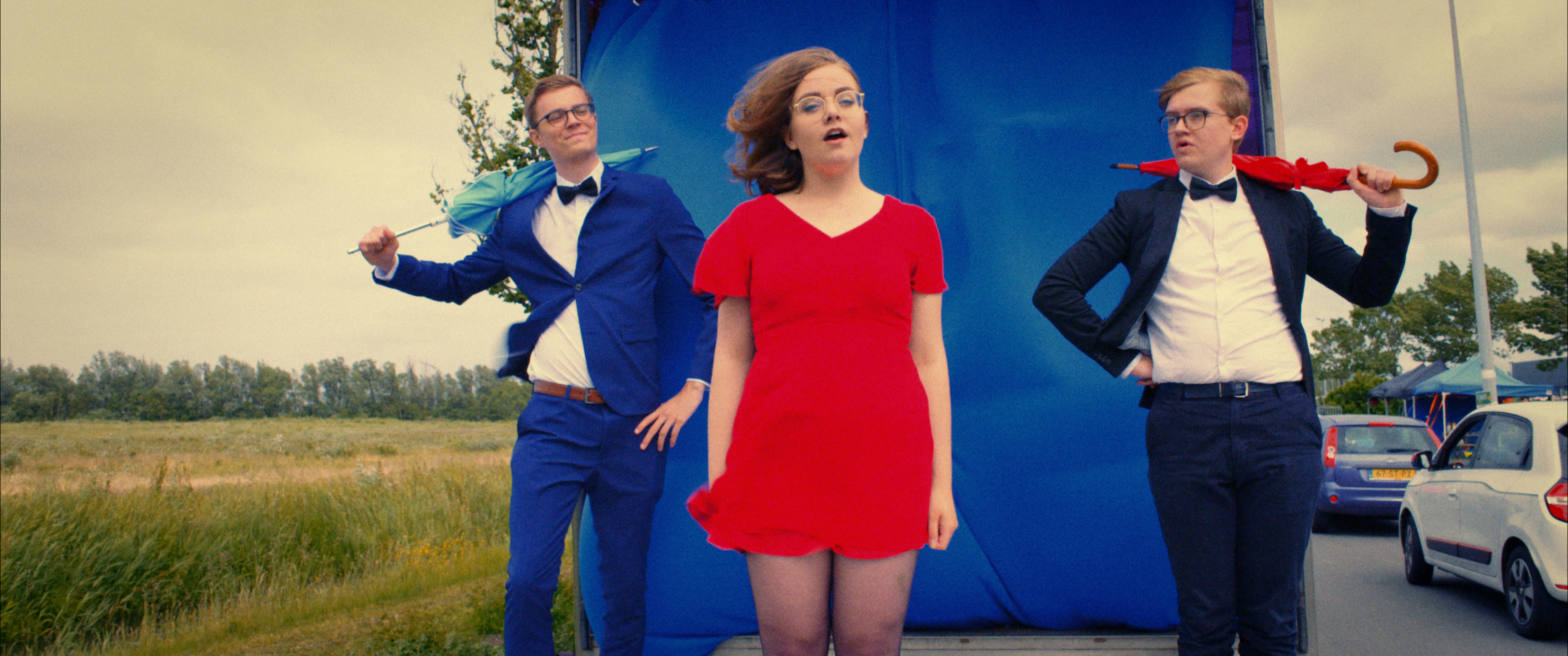 Still from the promo film Nieuwe Dag Op Set. Three people are standing on the loading deck of a truck. They are wearing fancy clothes. The girl in the front, me, is singing and the two boys besides her are holding umbrellas.