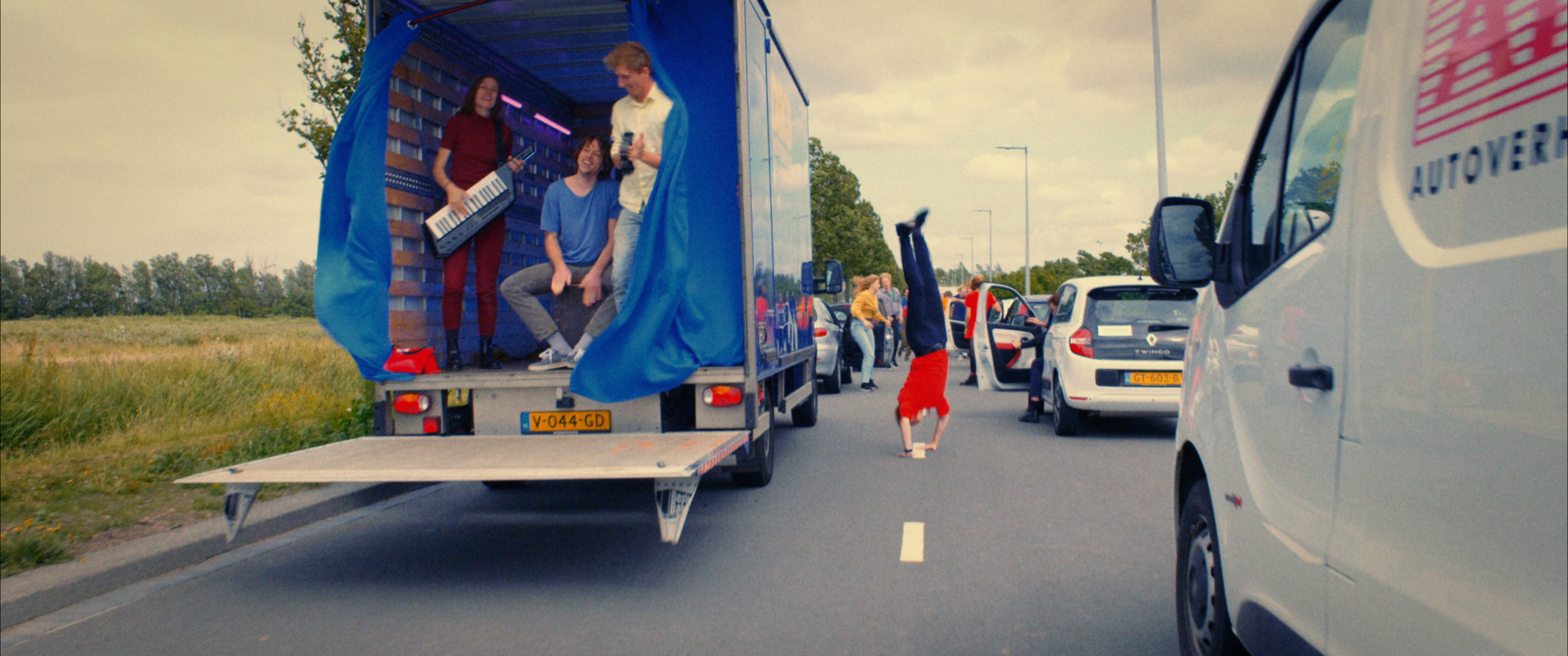 Still from the promo film Nieuwe Dag Op Set. It's a shot of two lanes of traffic. There is a band playing in the back of the truck and one guy is doing a cartwheel in between the lanes.