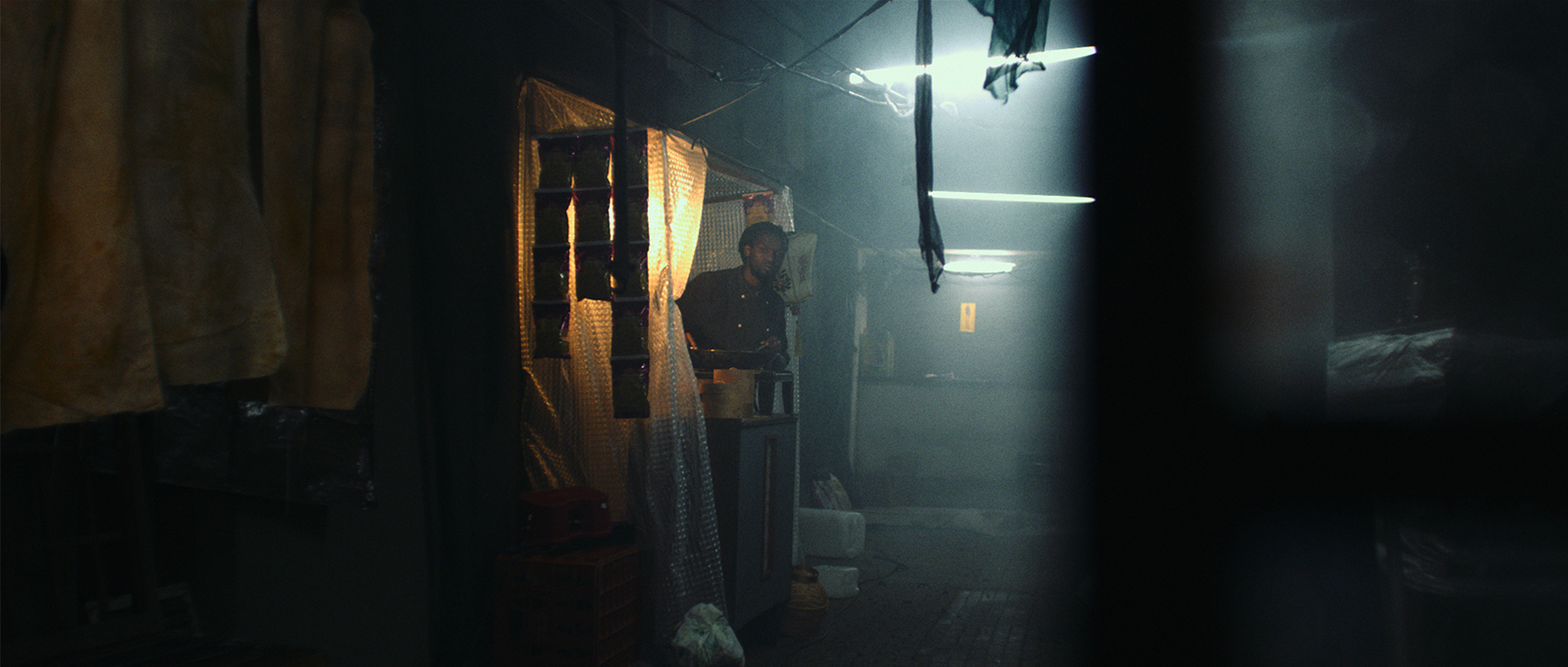 Still from the film Ningyo. It's a shot of a dark back ally. An outside cook is looking in the direction of the camera.