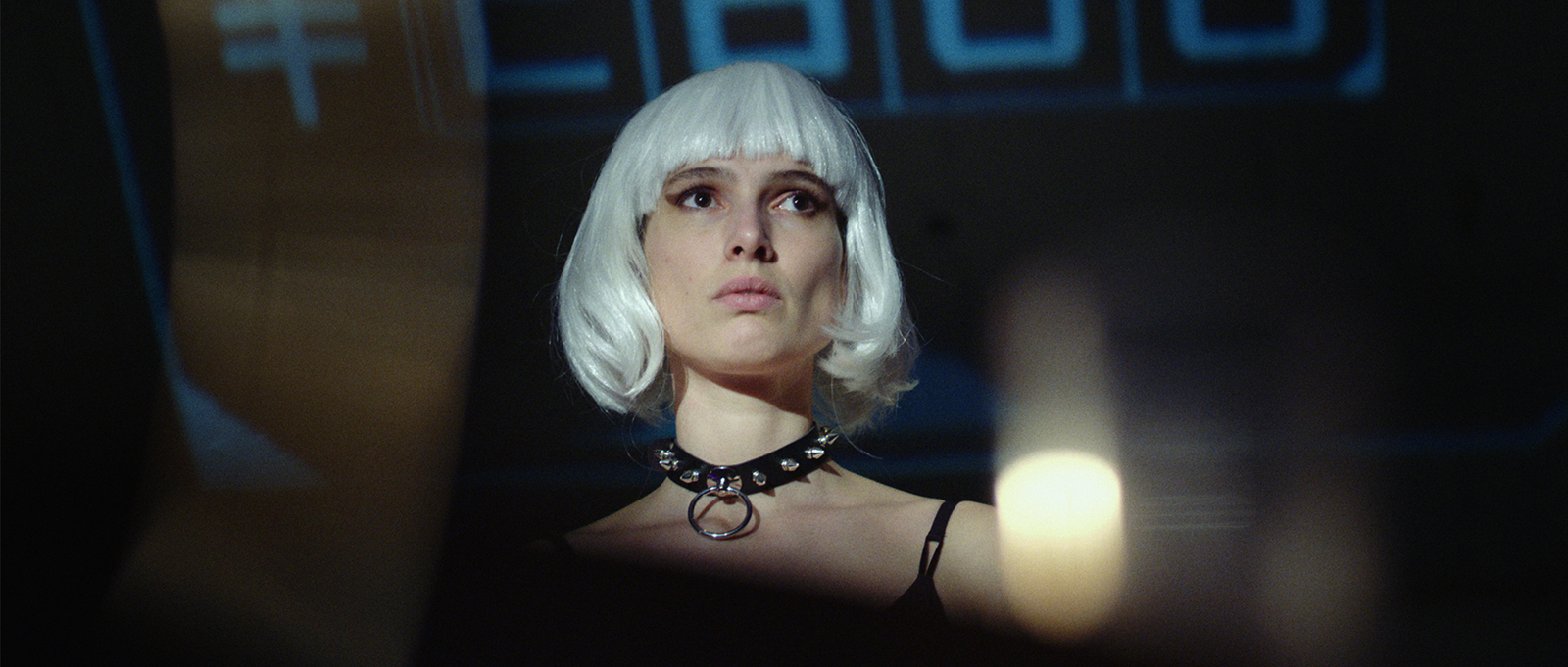 Still from the film Ningyo. It's a low angle close-up of a girl with a silver/white wig on. She's wearing a collar.
