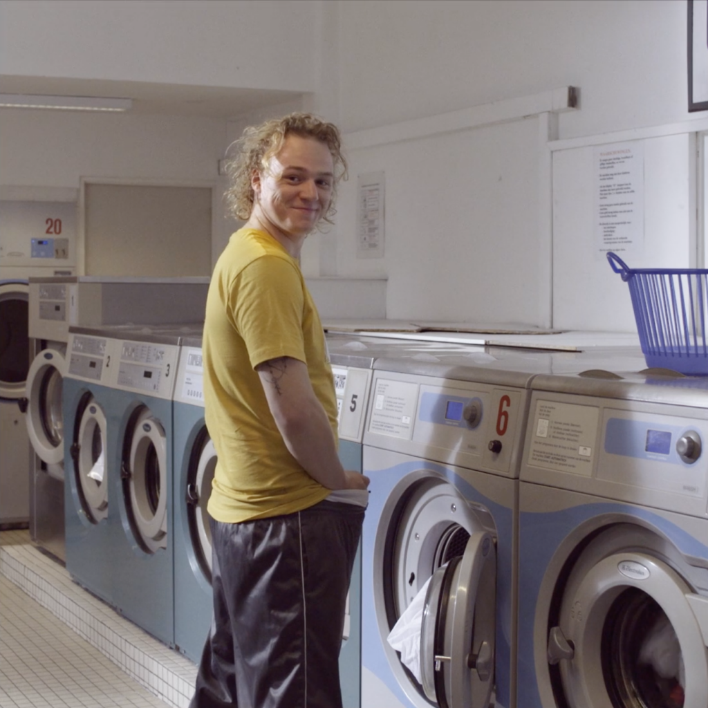 Still of the commercial Wasserette. A guy is standing in front of a washing machine in a laundrette. He's looking back and smiling.
