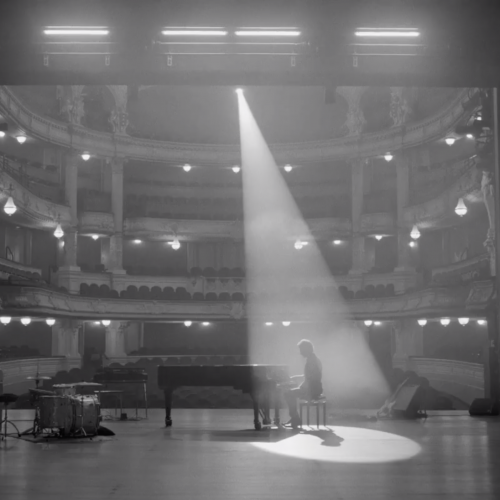 Still from the music video for Maarten Heijmans & Band - Sammy. Maarten is sitting behind a grand piano on the stage of the International Theater Amsterdam. There's a spotlight on him.