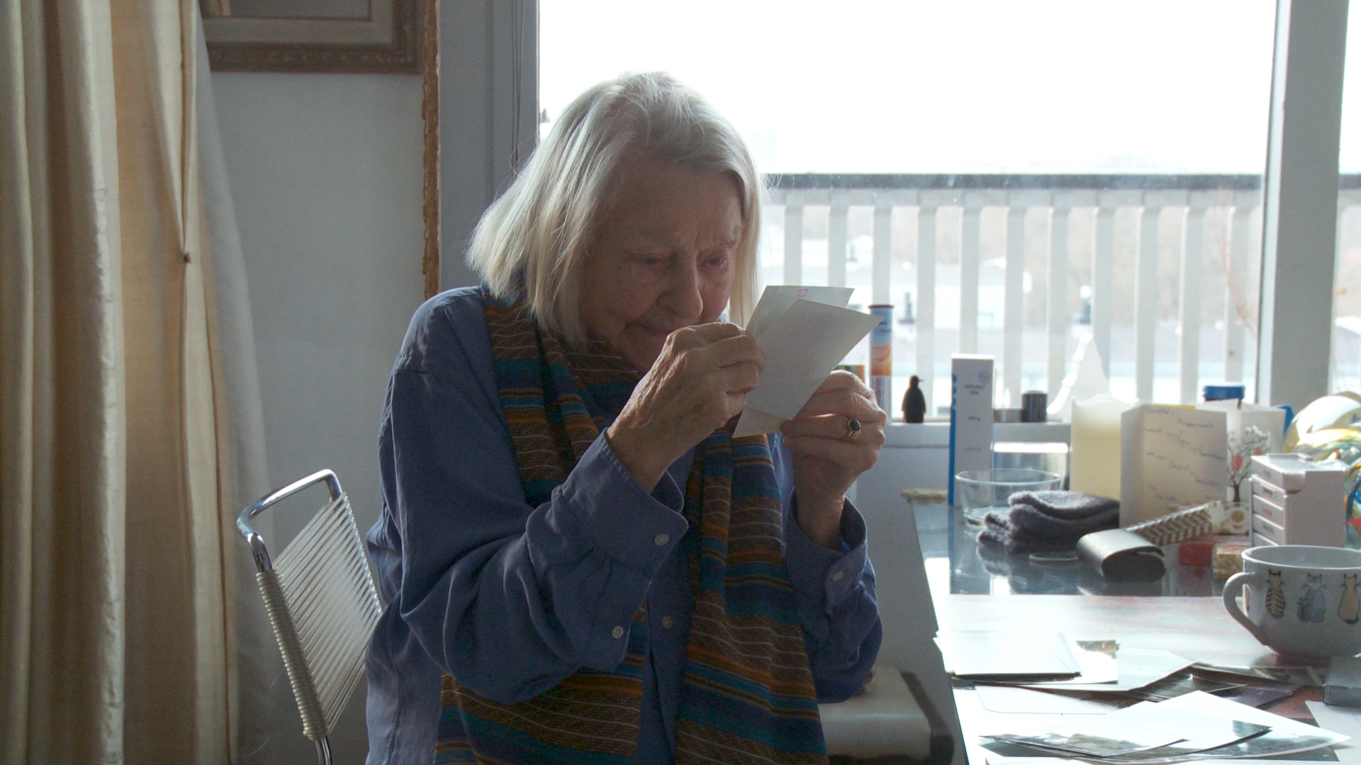 Still from the film Een klein beetje nog. Elisabeth is sitting at her dining table looking at old pictures.