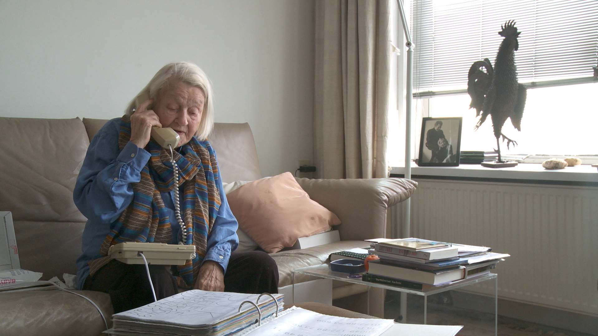 Still from the film Een klein beetje nog. Elisabeth is sitting on her couch on the phone.