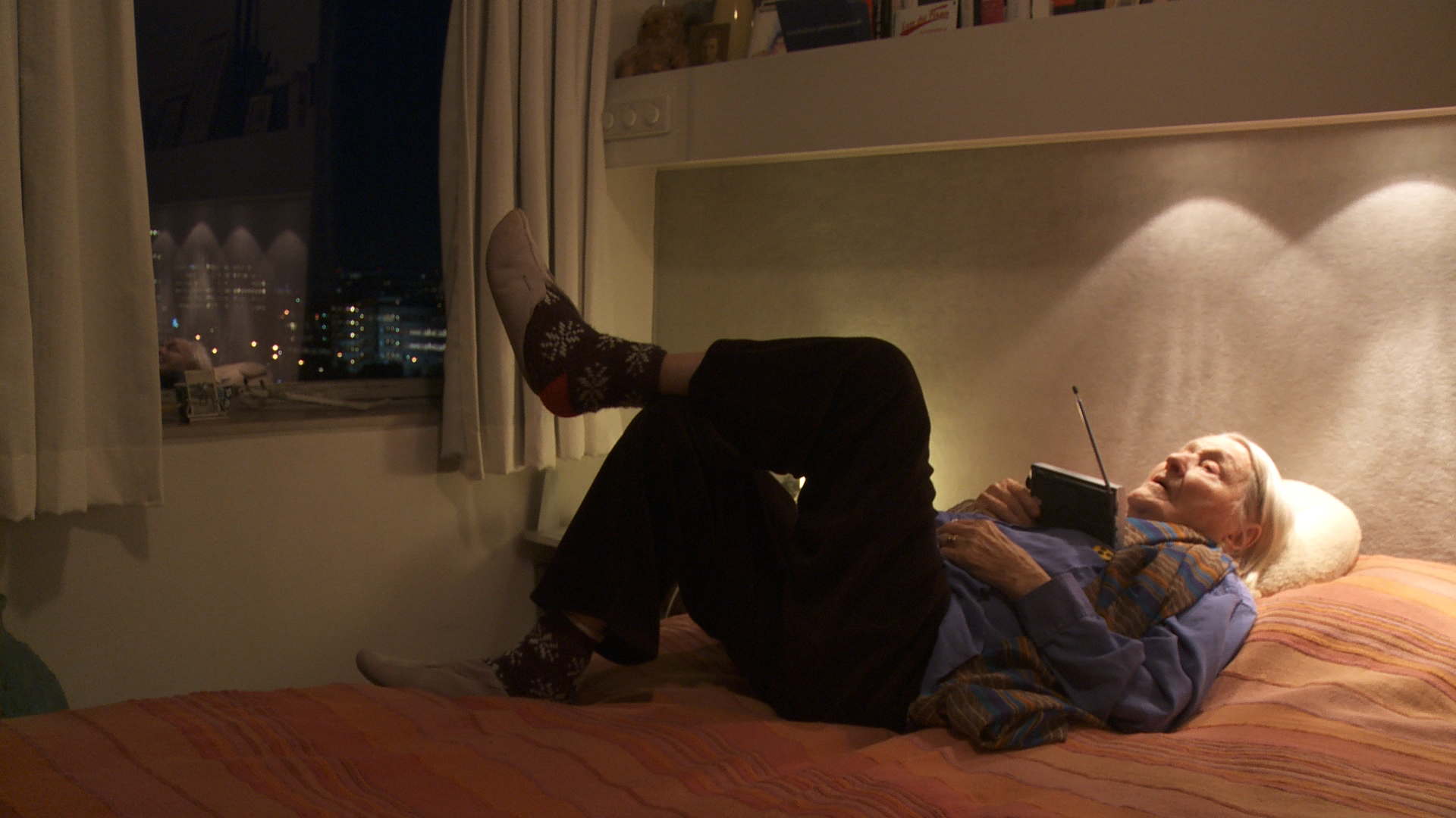 Still from the film Een klein beetje nog. Elisabeth is lying on her bed, one foot propped up on her other knee, listening to the radio.
