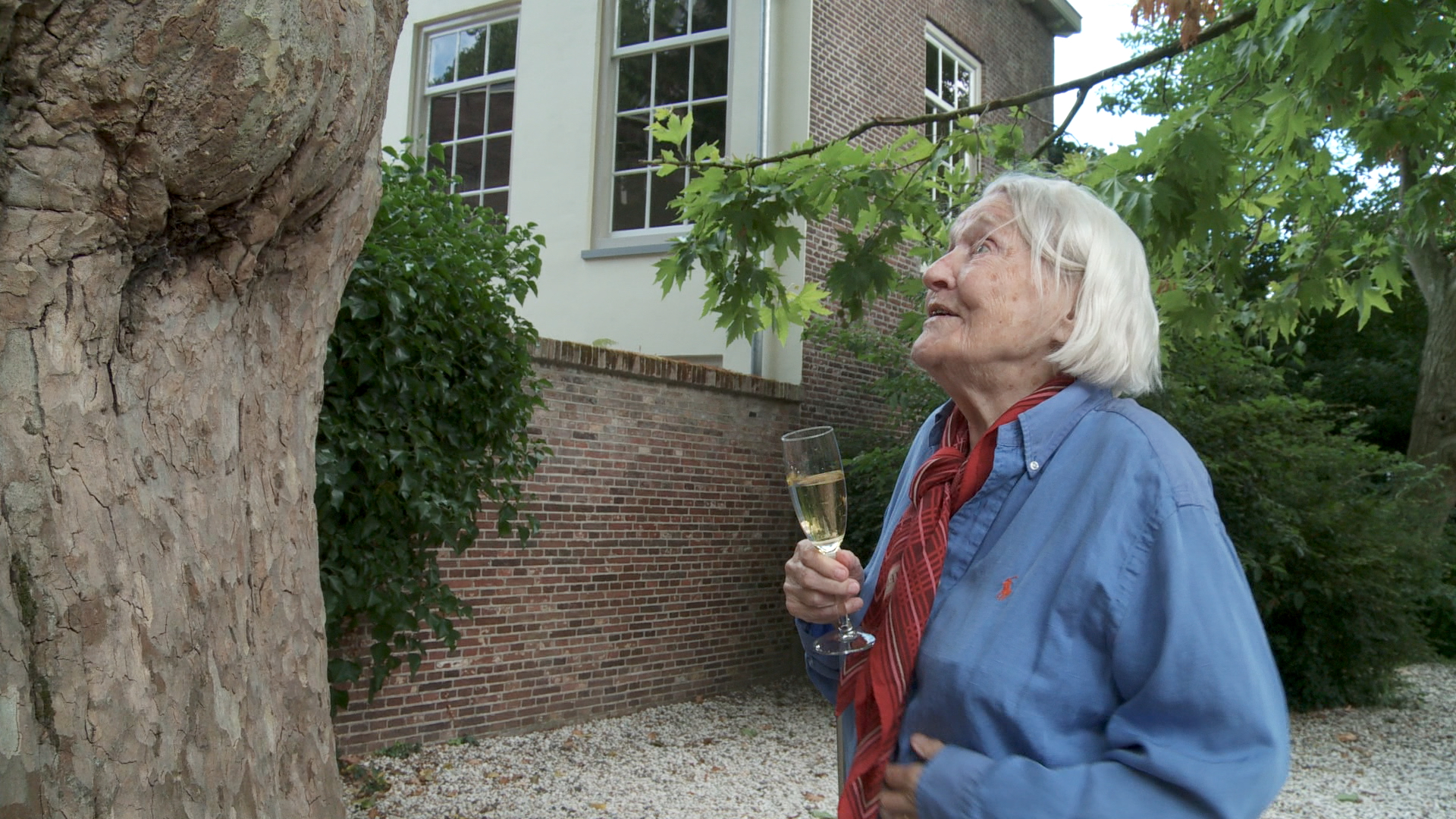 Still from the film Een klein beetje nog. Elisabeth is standing at an old tree with a glass of champagne in hand. She looks happy.