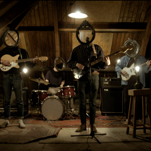 Still from the music video for The Hazzah - I'm Your Man. The band is standing in an attic performing, but their heads are all mirrors.