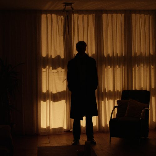 Still from the film Van Binnenuit. A silhouette is standing in a living room.