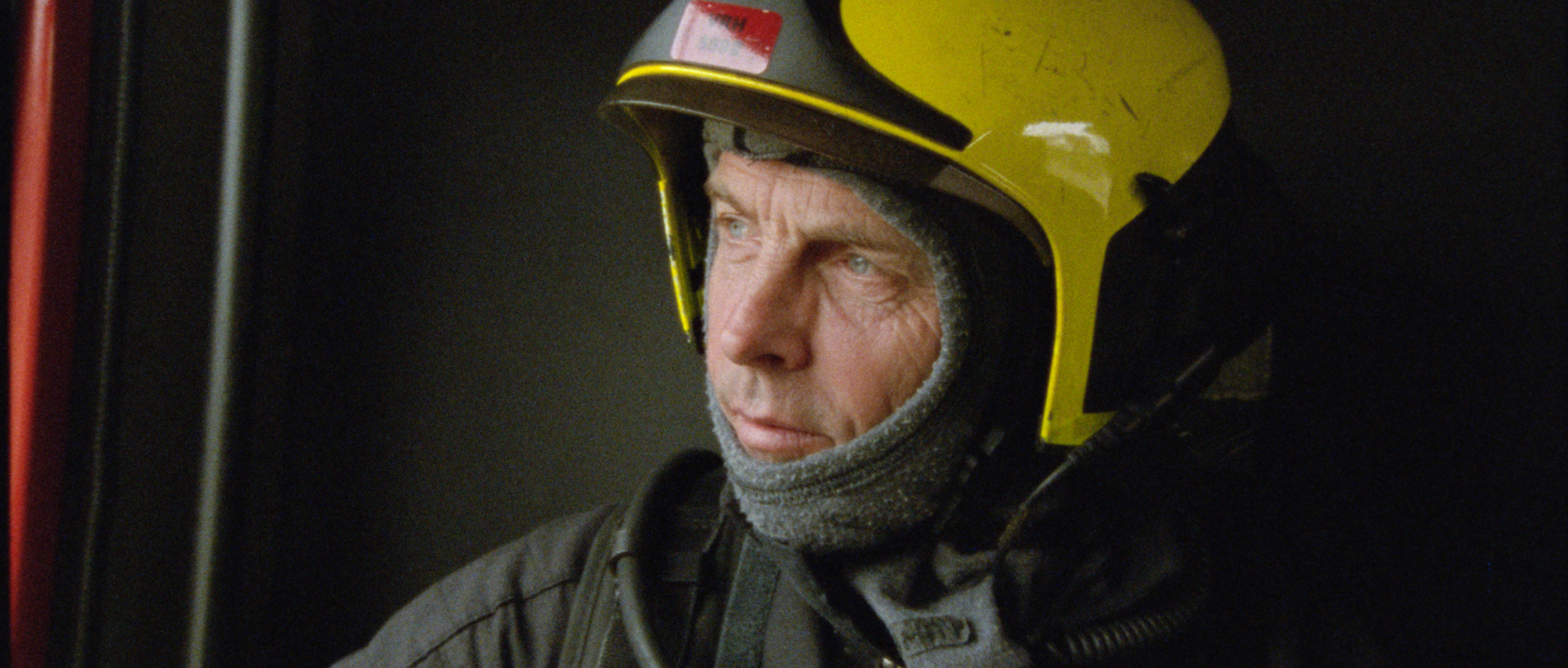 Still from the film Door Het Vuur. A firefighter is sitting in a firetruck. His a close-up and he is looking out the window.