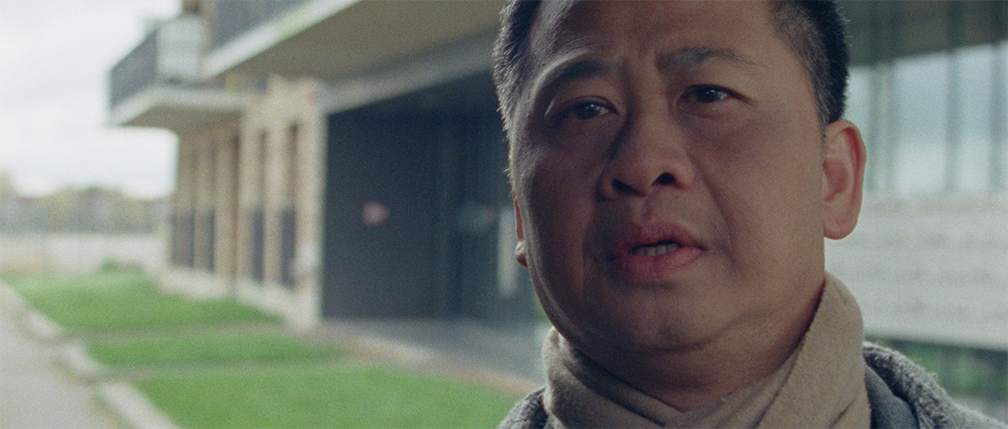 Still from the film Geen woord voor ons. It's a close up of Dung's face while he looks off screen in the distance.
