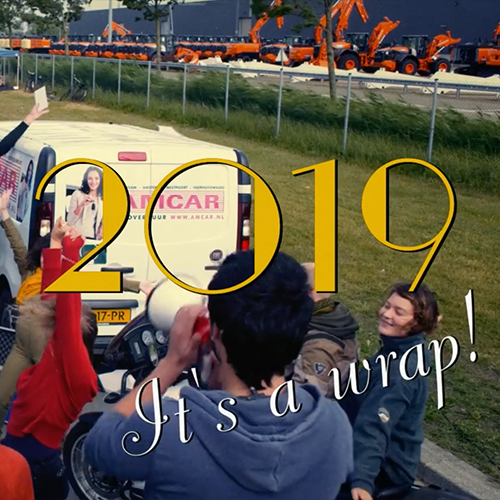 """Thumbnail the promo film Nieuwe Dag Op Set. There's some cars in the background and people's back turned to the camera in the foreground. There's a title that says """"2019, it's a wrap!""""."""