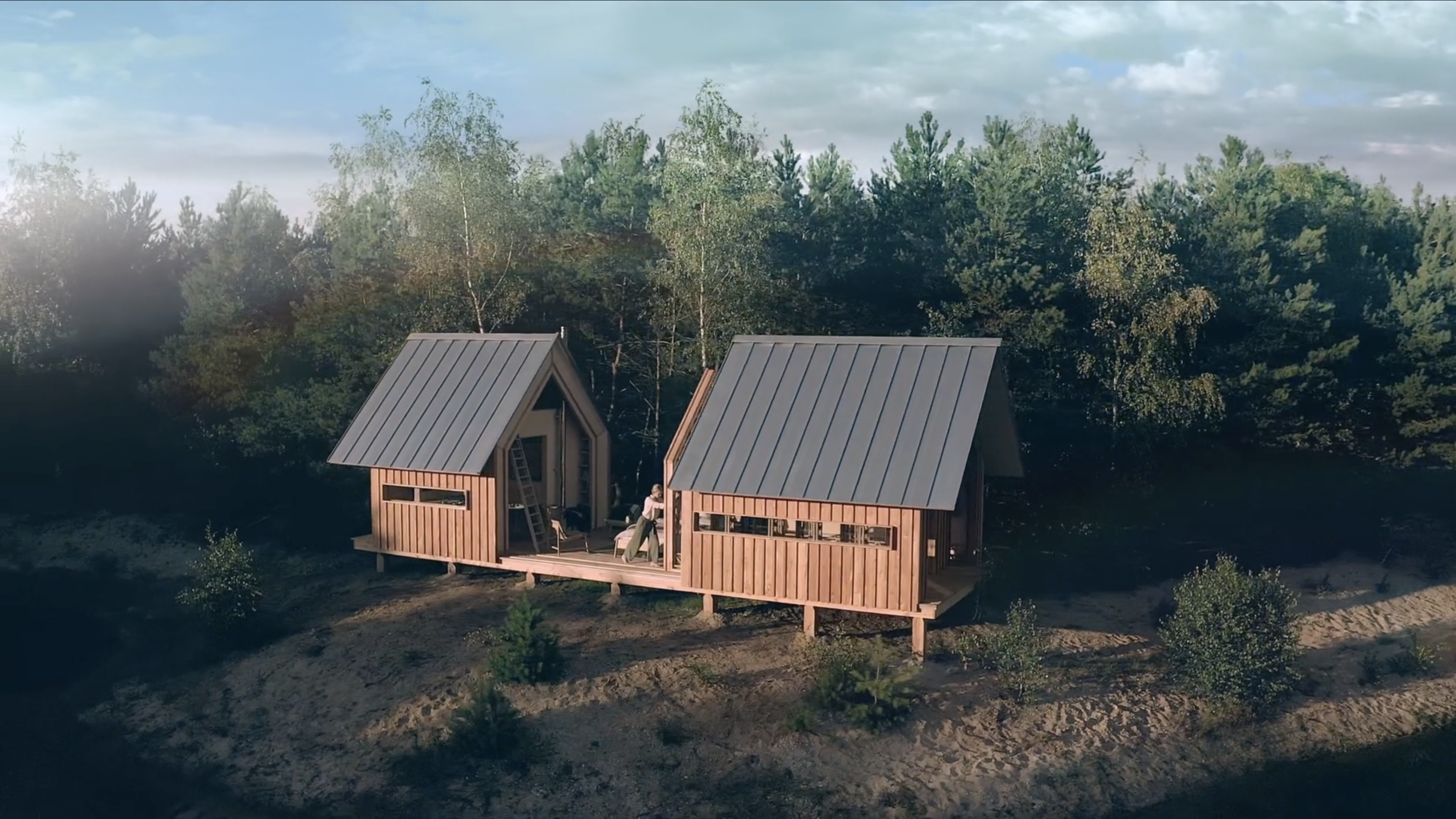 Still from Cabin ANNA Stay. It's a wide shot of the ANNA STAY cabin. The girl in the video is pushing open the inner layer of the cabin, so the whole inside of the cabin is in the sunlight. It is sunny.