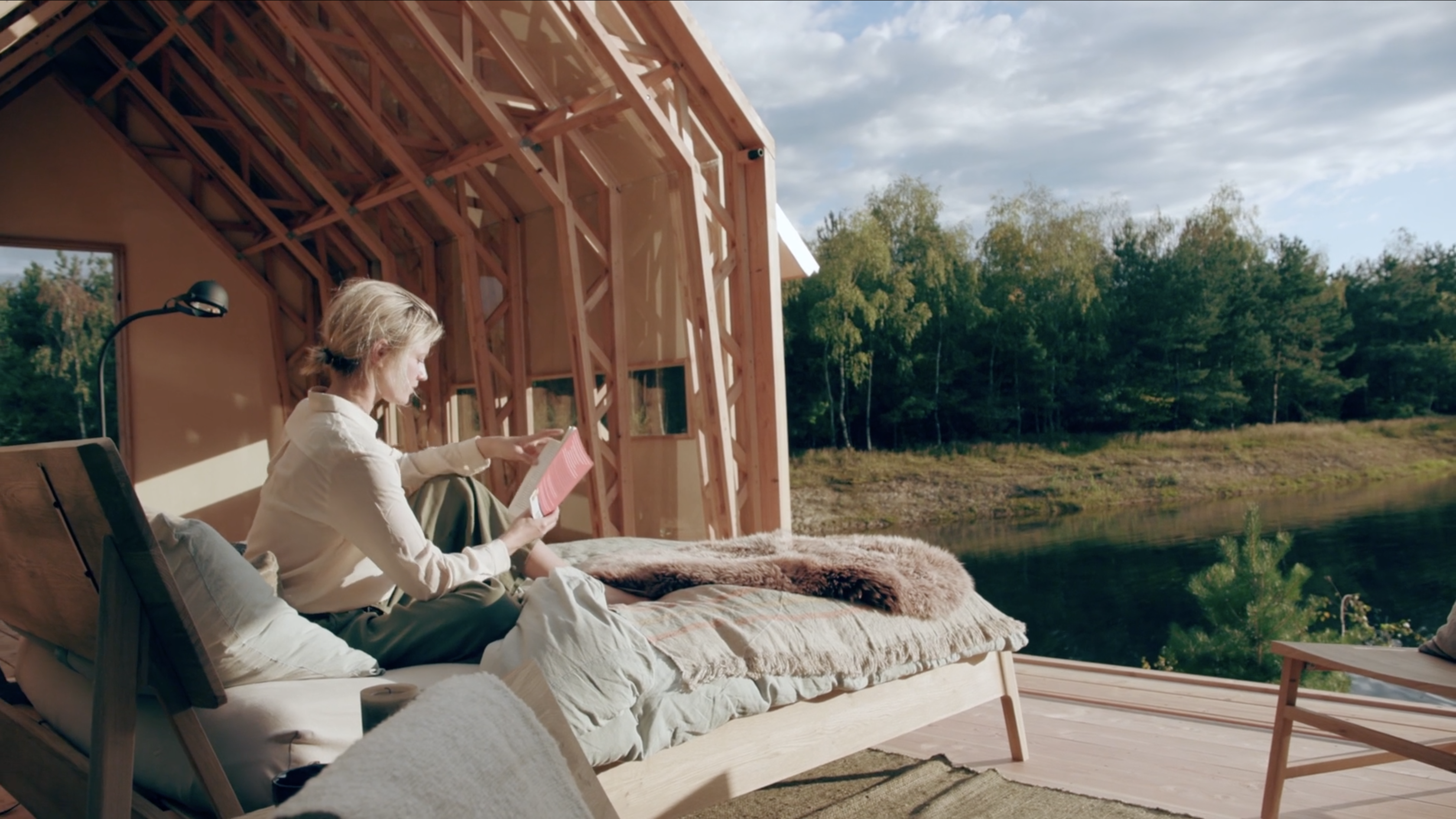 Still from Cabin ANNA Stay. It's a medium shot of the inside of ANNA STAY. The girl in the video is sitting on the bed, reading a book in the sunlight, 'outside'.