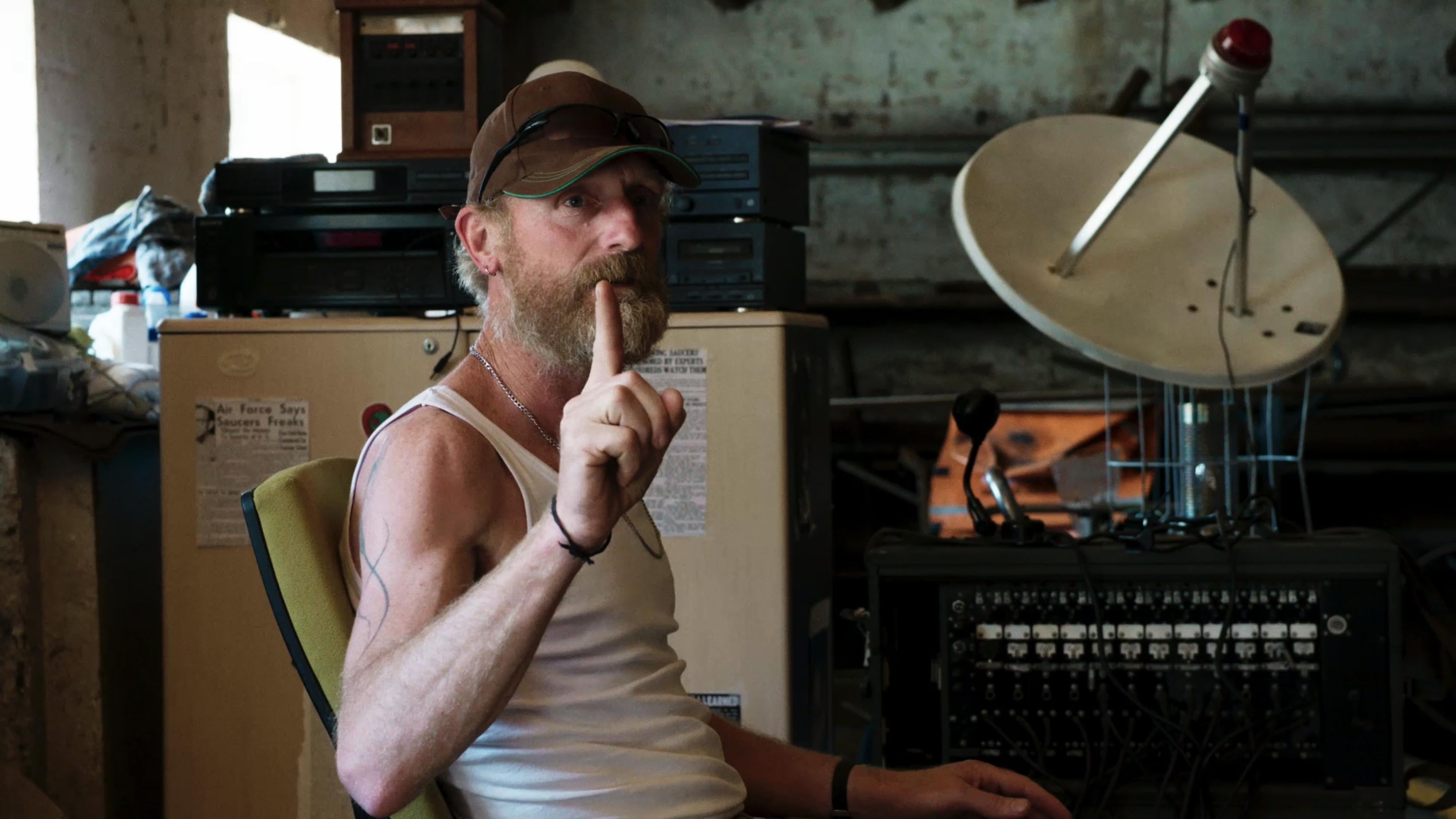 Still from 'Wat we niet wisten over koeien'. Ben is sitting in front of a weird contraption with a satellite on it. He's holding his index finger up, as if to signify 'listen!'.