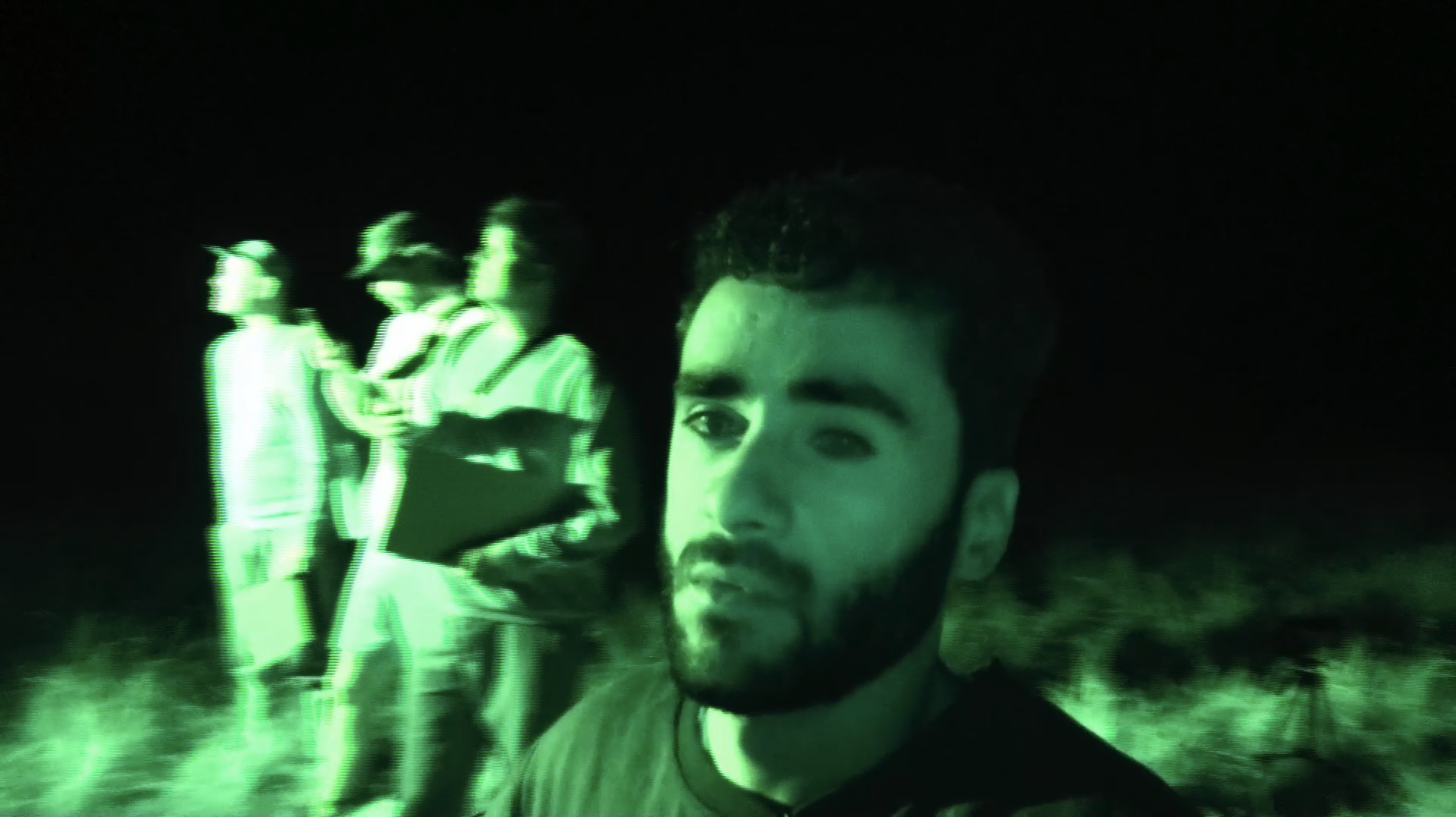 Still from 'Wat we niet wisten over koeien'. It looks like a nightvision camera; the whole screen is green. Soner is looking into the camera, bewildered. The rest of the crew is in the background.
