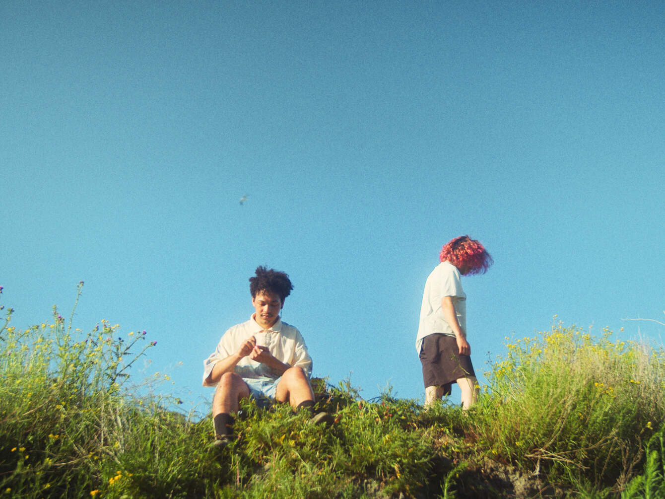 Still from Incendios. A wide shot of the two boys on some grass on a small hill. The sky is bright blue.