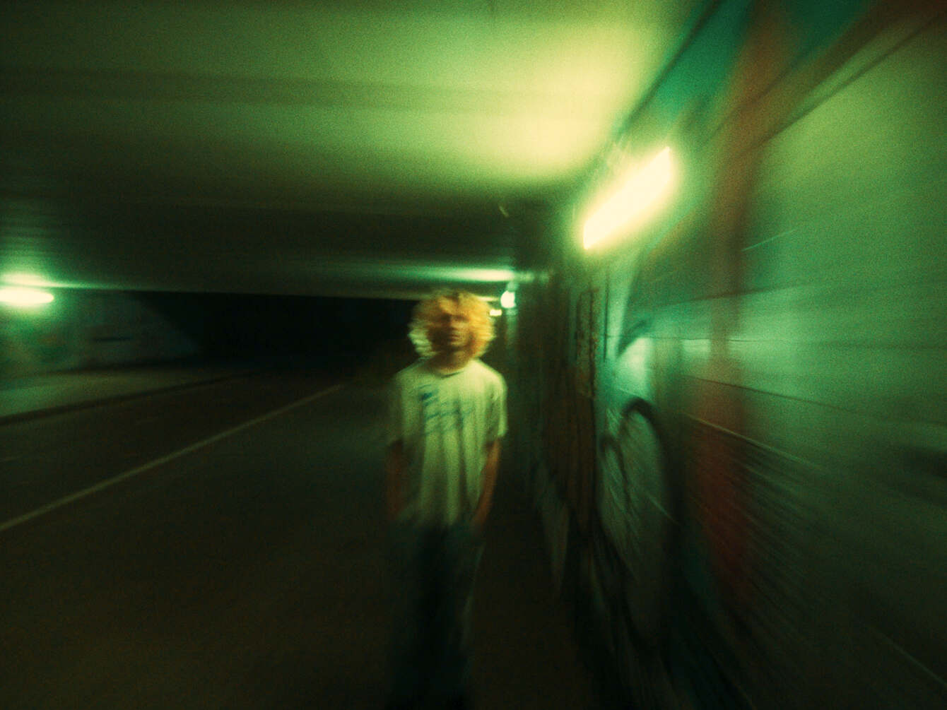 Still from Incendios. One of the two boys, played by Dmitri, is standing in a tunnel with graffiti on the wall. The shot is very blurry, as if it's in motion.