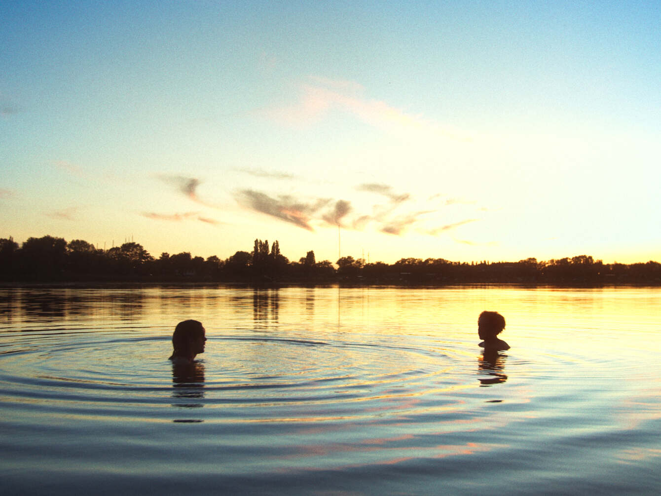 Still from Incendios. A wide shot of the two boys in a lake, facing each other with some distance in between them. The sun is setting.