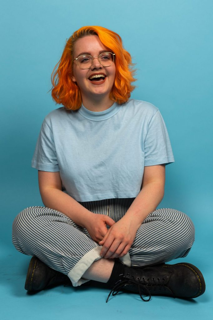 Picture of Eva sitting crossed-legged in a light blue studio space. She's has bright orange hair, blue eyes and is wearing thin, gold-rimmed circular glasses. She's wearing a light blue cropped t-shirt, blue-and-white striped jeans and Dr Marten shoes. She's laughing and looking off to the side.