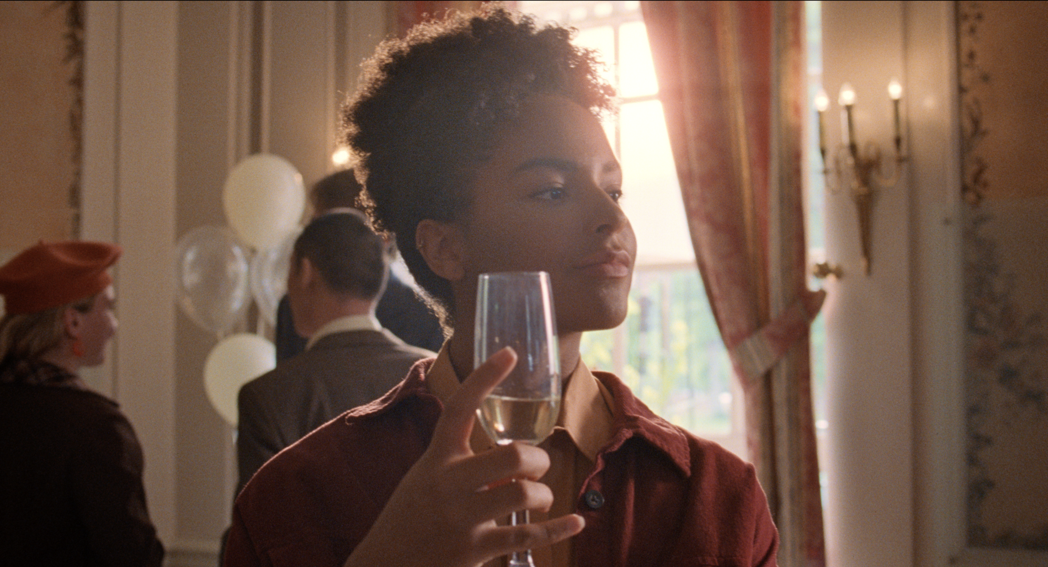 Still from the commercial For You. It's a close up of Eden looking off screen. They have a glass of champagne in their hand.