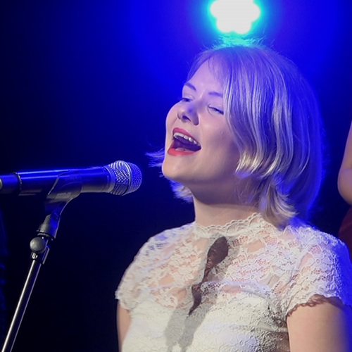 Thumbnail for Groei - Suzanne de Jong. Suzanne is standing in front of a microphone singing. She has shoulder length blonde hair, wears a white lacy top and is wearing red lipstick. Behind her is a blue light.