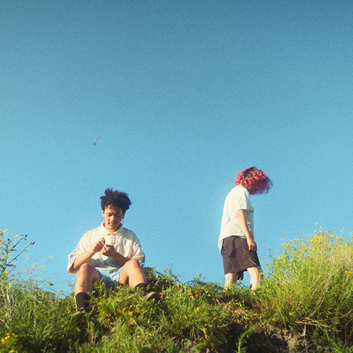 Thumbnail for Incendios. A wide shot of the two boys on some grass on a small hill. The sky is bright blue.