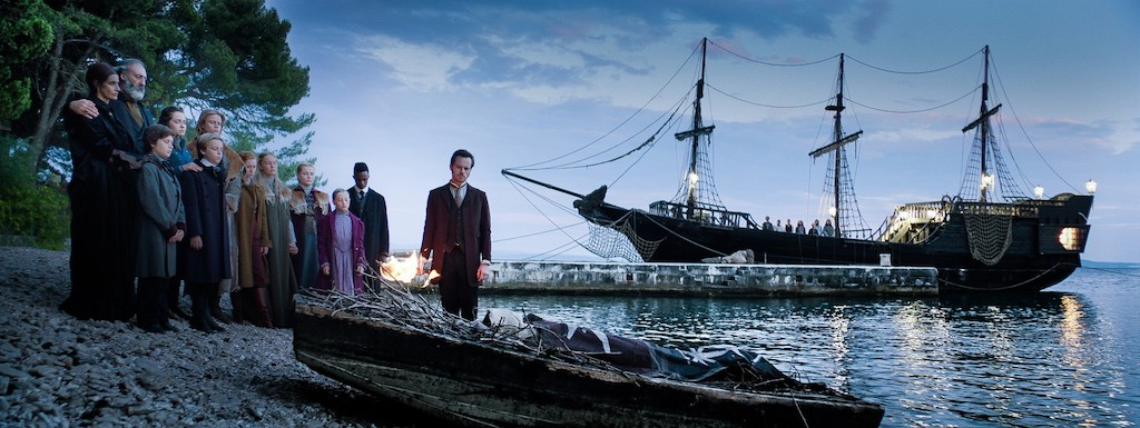 Still from Heirs of the Night. Wide shot at the beach, with the Elisabetha in the background. The vampires are standing on the beach, looking sadly at an oar on the shore.