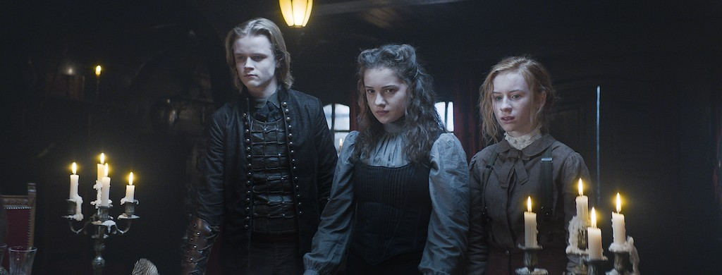Still from Heirs of the Night. Medium shot of Lars, Alisa and Ivy standing at a table, a confrontational look in their eyes.