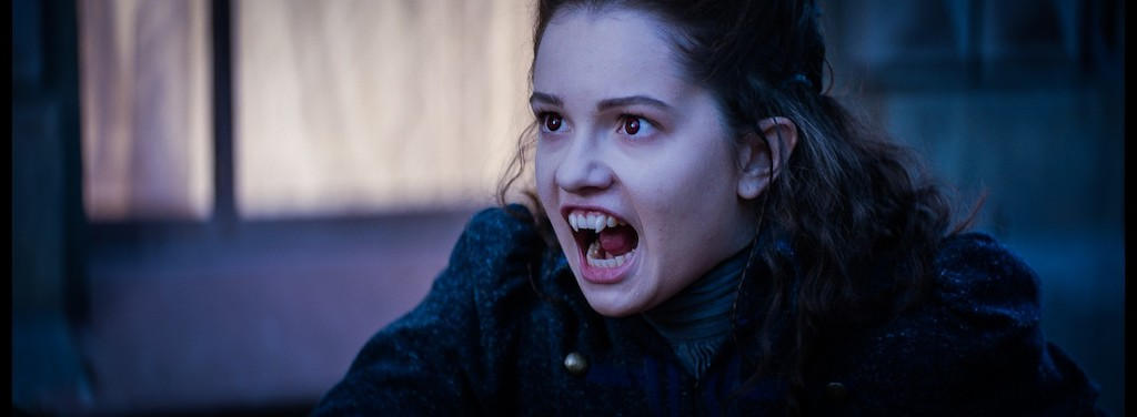 Still from Heirs of the Night. Close-up of Alisa, who's looking ferocious with her mouth open and fangs out.